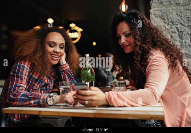 Porträt der jungen Frauen sitzen in einem Café mit Handy. Zwei junge Mädchen eine SMS auf dem Handy Stockbild