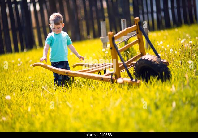 Kleiner Junge in den Bereichen tätig und Schubkarre Stockbild