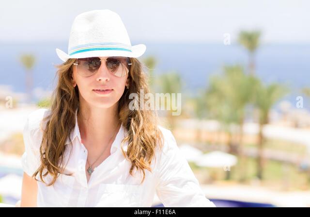 Junge Dame mit Urlaub im tropischen Resorthotel. Schöne kaukasische Mädchen trägt Sonnenbrille und Stockbild