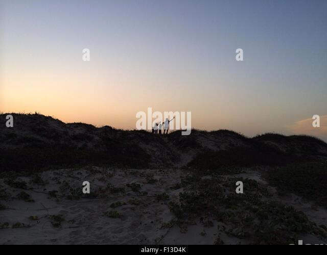 Silhouette von vier Menschen, die stehen auf einer Sanddüne Stockbild