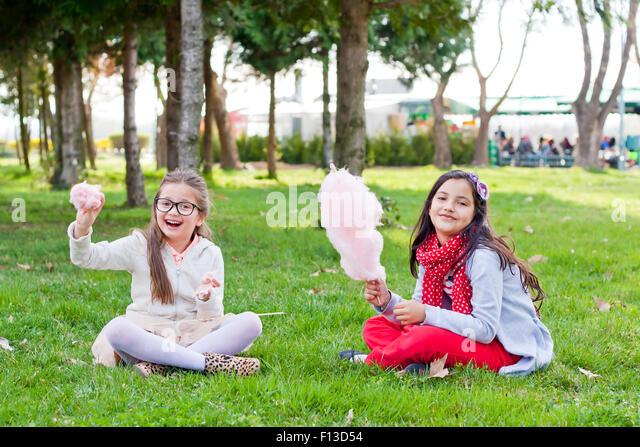 Zwei Mädchen sitzen im Park essen Zuckerwatte Stockbild