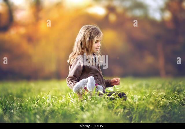 Mädchen sitzen in einem Feld mit einem Stofftier Stockbild