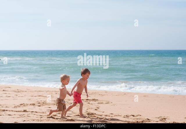 Zwei jungen Hand in Hand am Strand Stockbild