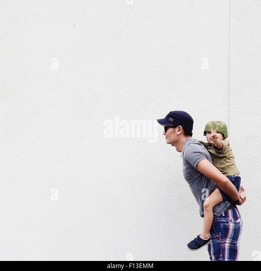Vater geben seinem Sohn eine Huckepack Fahrt Stockbild