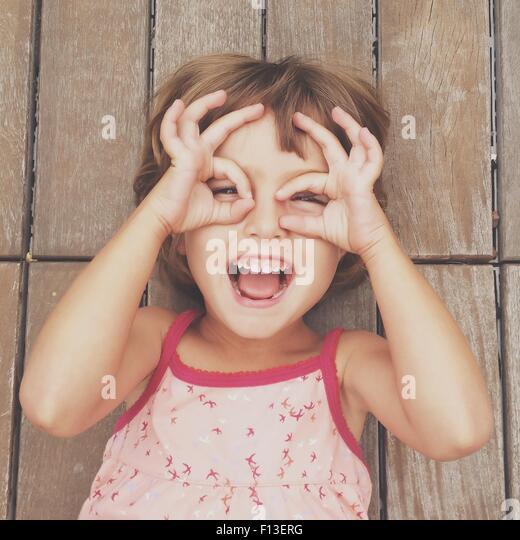 Mädchen auf der Suche durch die Finger frames Stockbild