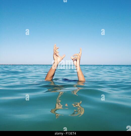 Menschliche Hände kommen aus dem Meer Stockbild