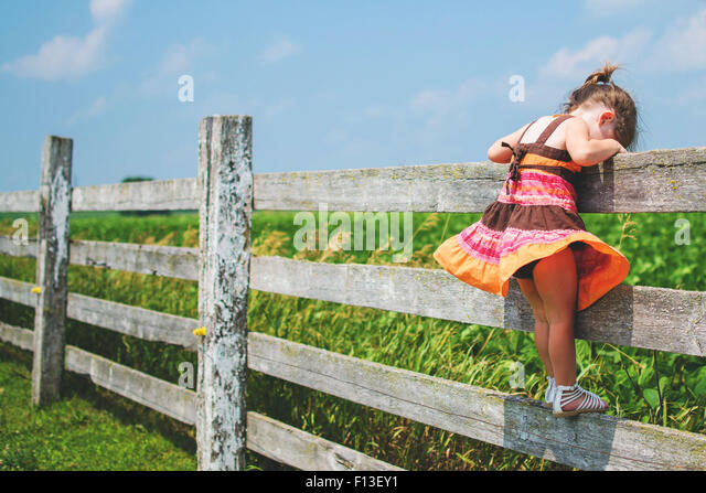 Seitenansicht eines Mädchens auf einem Zaun blickte stehend Stockbild