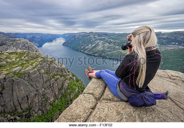 Frau sitzt auf dem Rand des Preikestolen fotografieren, Norwegen Stockbild