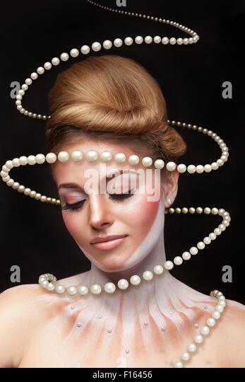 Surreale Kunst-Konzept von Mädchen mit Perlen rund um sie. Studio Aufnahmen. Surrealismus und Concept art Stockbild