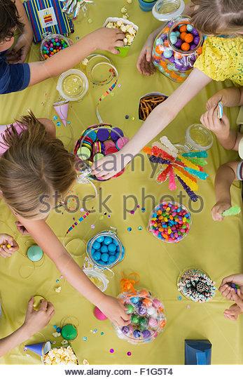 Draufsicht Kinder erreichen Süßigkeiten-Tabelle-Geburtstags-party Stockbild