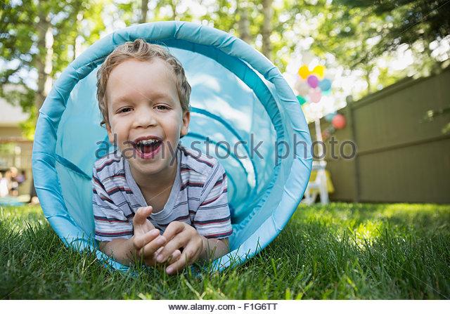 Porträt lächelnden jungen Spielzeug Tunnel im Hinterhof Stockbild