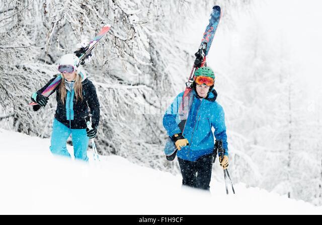 Mann und Frau zu Fuß im Schnee mit Skiern Stockbild