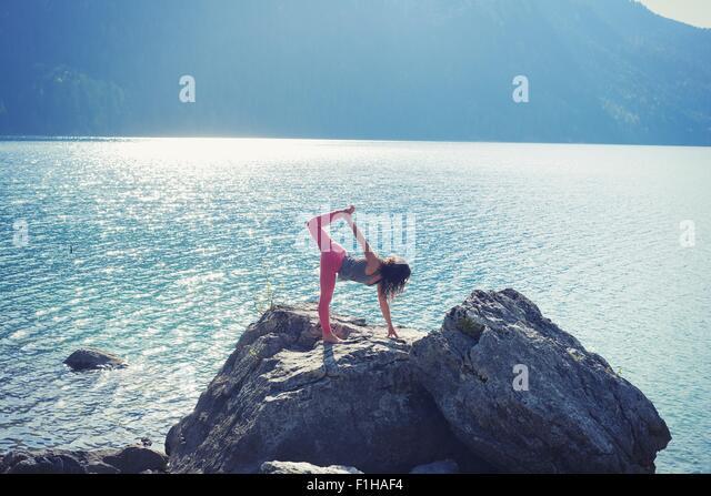 Mitte Erwachsene Frau, balancieren auf Rock am See in Yogaposition Stockbild