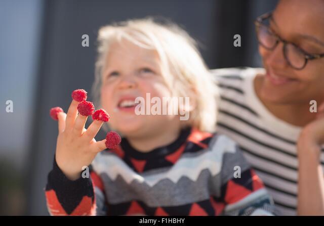 Junge mit Himbeeren an Fingern, Mutter beobachten Stockbild