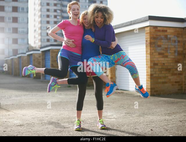 Porträt von drei Frauen tragen sportliche Kleidung springen Stockbild