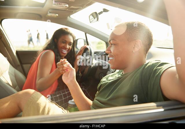 Junges Paar sitzt im Auto, die Hand in Hand Stockbild