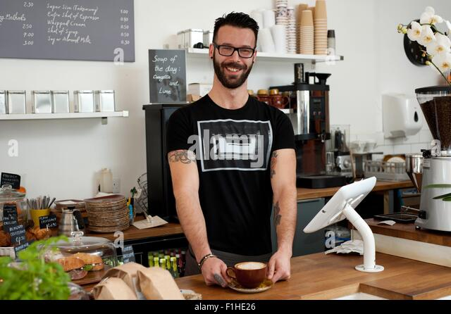 Porträt des Café Kellner serviert Kaffee vom counter Stockbild