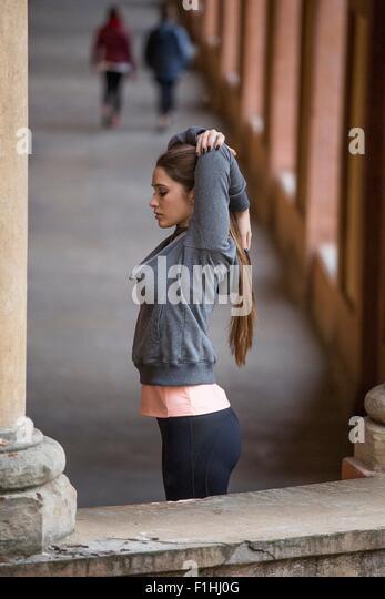 Junge Frau trägt Sportkleidung Strecken Arme Stockbild