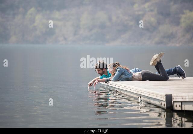 Junges Paar liegen am Pier Eintauchen der Finger in Mergozzo See, Verbania, Piemont, Italien Stockbild