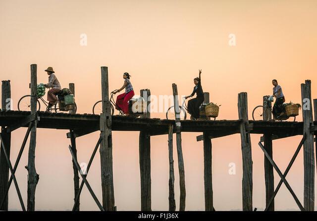 Burmesische Frau blinkt Peace-Zeichen auf einem Fahrrad fahren über U Bein Brücke bei Sonnenuntergang. Stockbild