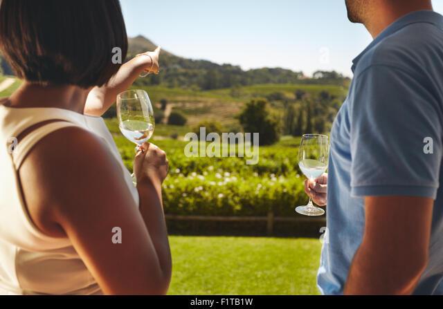 Junges Paar im Urlaub mit einem Glas Wein, mit Frau zeigt entfernt am Weinberg, zeigen etwas zu ihrem Freund. Stockbild