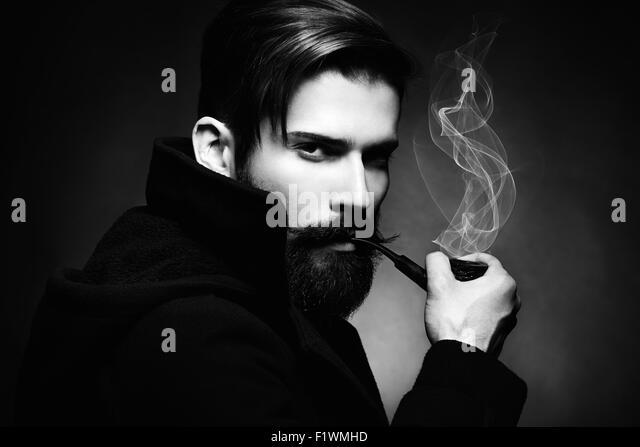 Künstlerische dunkle Porträt des schönen Jünglings. Der junge Mann raucht ein Rohr. Hautnah. Stockbild