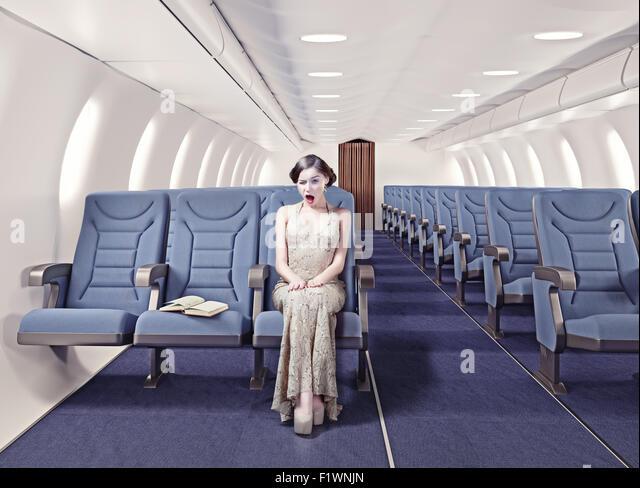 Überrascht Mädchen in einem Flugzeug. Kreativkonzept Stockbild