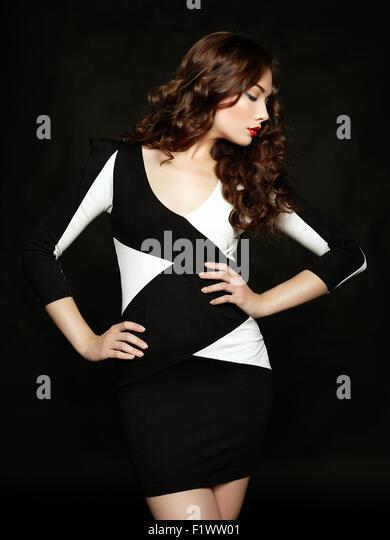 Porträt von schöne Brünette Frau im schwarzen Kleid. Modefoto Stockbild