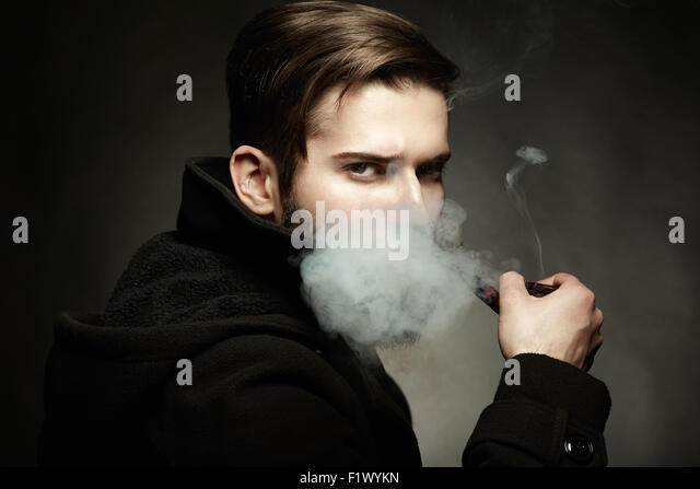 Künstlerische dunkle Porträt des schönen Jünglings. Der junge Mann raucht ein Rohr. Nahaufnahme Stockbild