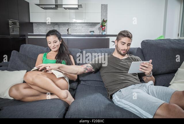 Junger Mann mit Freundinnen Buch auf sofa Stockbild