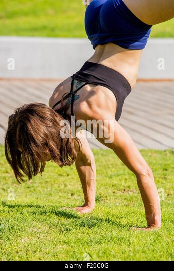 Junge Frau tun Handstand im park Stockbild