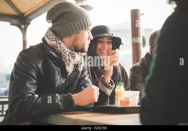 Vier junge Erwachsene Freunde plaudern und Essen Donuts im Straßencafé Stockbild