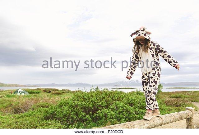 Mädchen tragen Tier Onesie balancieren auf Holzzaun, Thingvellir, Island Stockbild