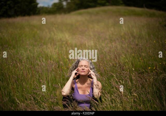 Reife Frau mit Fingern auf ihre Tempel sitzen in langen Rasen zu meditieren Stockbild