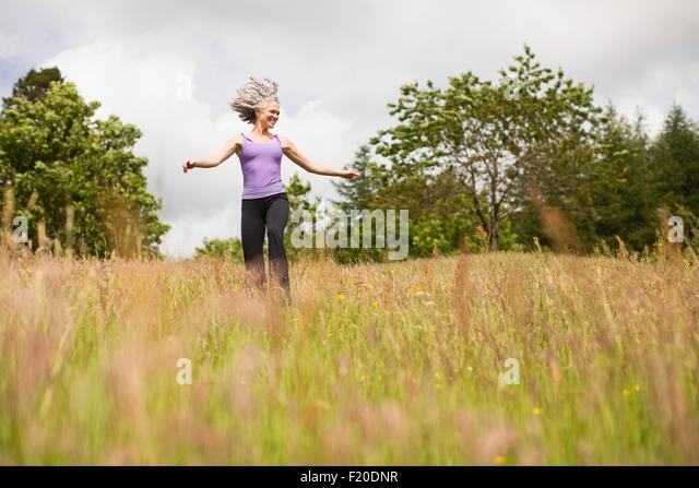 Reife Frau mit langen grauen Haaren durch Feld Stockbild