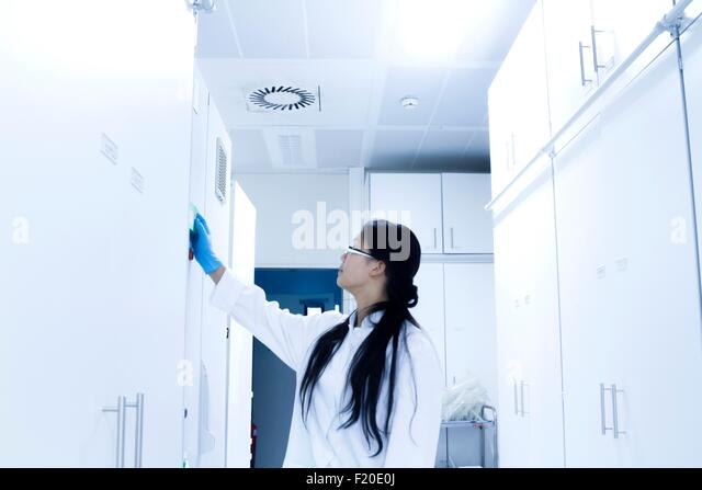 Wissenschaftlerin Eröffnung Probe Schrank im Labor Stockbild