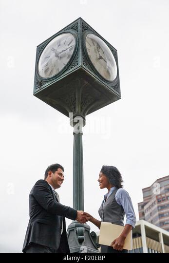 Niedrigen Winkel Ansicht Seitenansicht der Geschäftsleute Händeschütteln unter Uhr, Hüfte aufwärts Stockbild
