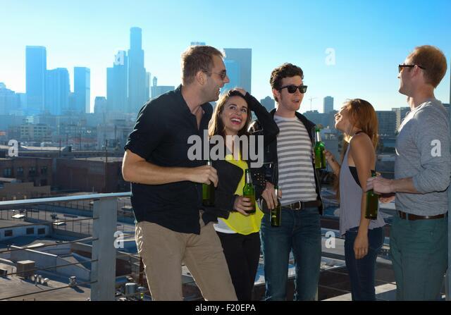 Fünf Erwachsene Freunde, flirten und trinken Bier an der Bar auf der Dachterrasse mit Skyline von Los Angeles, Stockbild