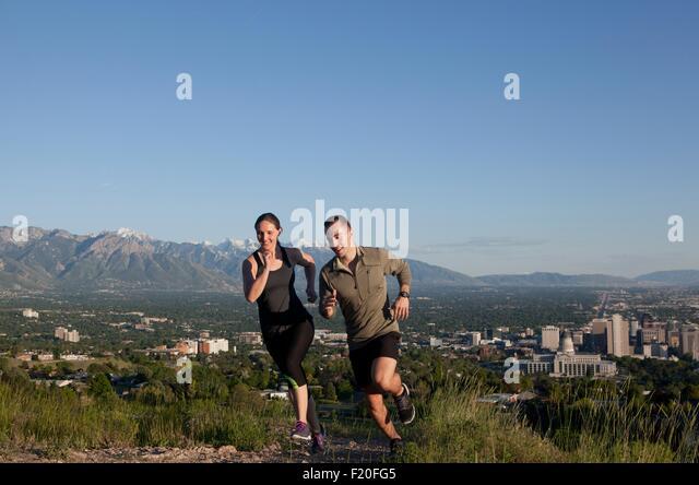 Junge weibliche und männliche Läufer Rennen entlang der Strecke über Stadt im Tal Stockbild