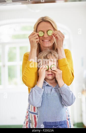 Mutter und Sohn, die Augen mit Gurkenscheiben bedecken Stockbild