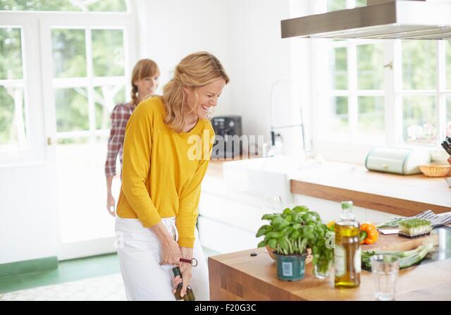 Frau, die Flasche Wein zu öffnen, in Küche Stockbild