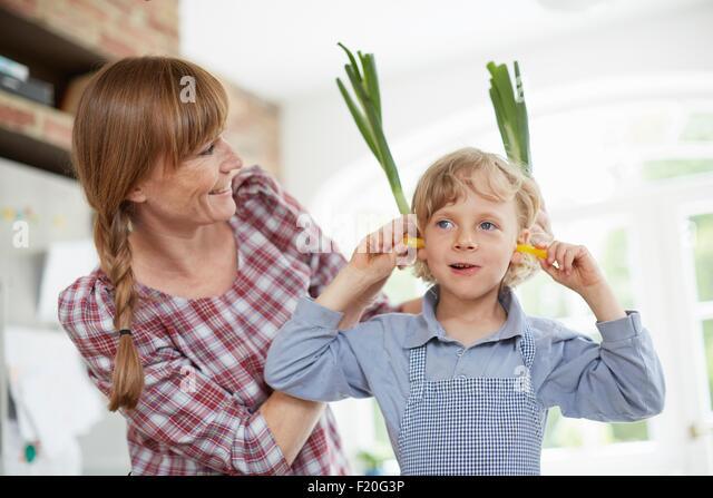 Mutter und Sohn spielt mit Gemüse in der Küche Stockbild
