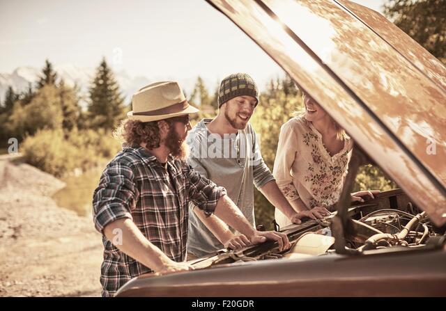 Drei Personen unter offenen Fahrzeug Haube an Motor Stockbild