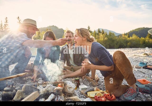 Mitte erwachsener Mann Reife Frau über einem Lagerfeuer Fütterung Stockbild