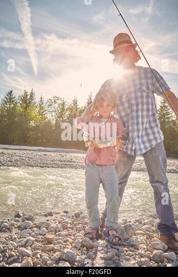 Mitte erwachsenen Mann und der junge neben Fluss stehend Angeberei Fisch, Blick in die Kamera Stockbild