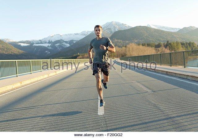 Junger Mann läuft auf Straße, Berge hinter ihm, Vorderansicht Stockbild