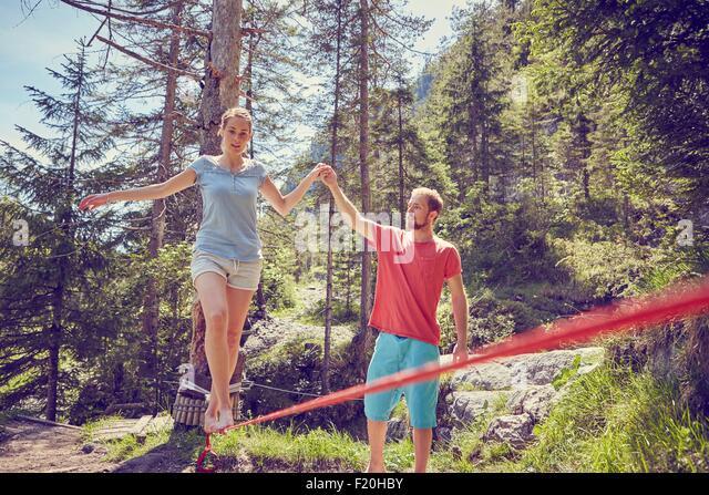 Frau balancieren auf Seil mit Hilfe von Mann, Ehrwald, Tirol, Österreich Stockbild