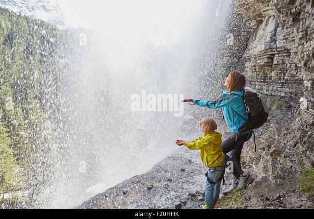 Mutter und Sohn, stehend unter Wasserfall, Hände zu spüren, das Wasser, die Sicht nach hinten Stockbild