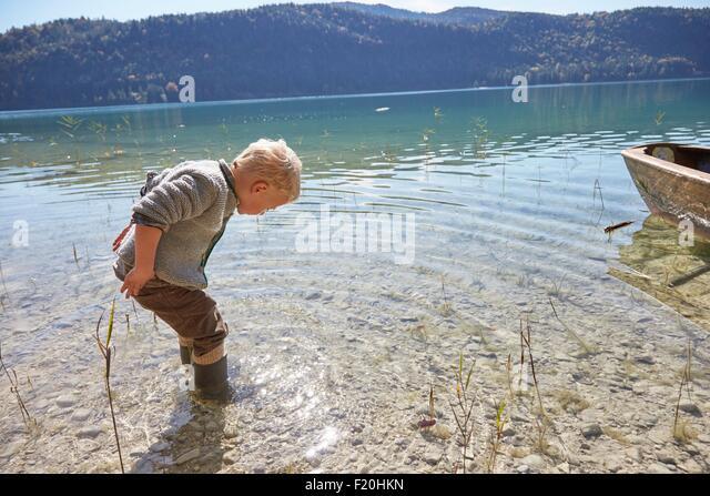 Junge paddeln und blickte in See, Kochel, Bayern, Deutschland Stockbild