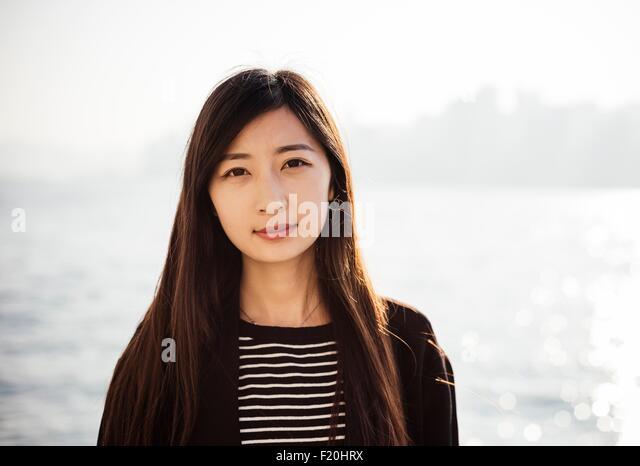 Porträt der jungen Frau mit lange brünette Haare tragen, gestreiftes Top Blick in die Kamera Stockbild